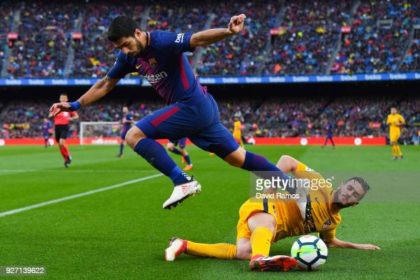 Luis Suarez of FC Barcelona competes for the ball with Koke Resurreccion of Club Atletico de Madrid during the La Liga match between Barcelona and...