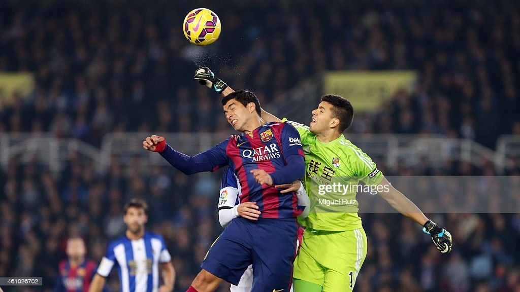 Luis Suarez of FC Barcelona competes for the ball with Rulli, goalkeeper of Real Sociedad de Futbol during the La Liga match between Real Sociedad de Futbol and FC Barcelona at Estadio Anoeta on January 4, 2015 in San Sebastian, Spain.