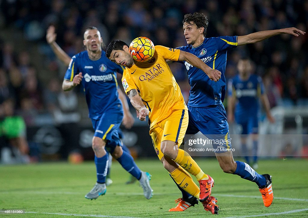 Luis Suarez (2ndR) of FC Barcelona competes for the ball with Santiago Vergini (L) of Getafe CF and his teammate Damian Suarez (R) during the La Liga match between Getafe CF and FC Barcelona at Coliseum Alfonso Perez on October 31, 2015 in Getafe, Spain.