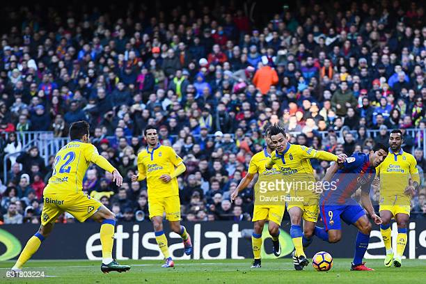 Luis Suarez of FC Barcelona competes for the ball with UD Las Palmas players during the La Liga match between FC Barcelona and UD Las Palmas at Camp...