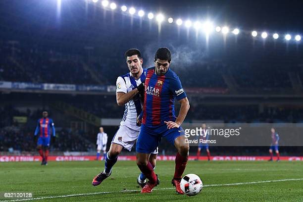 Luis Suarez of FC Barcelona competes for the ball with Yuri Berchiche of Real Sociedad de Futbol during the Copa del Rey quarterfinal first leg match...