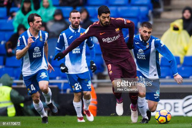 Luis Suarez of FC Barcelona conducts the ball under pressure from Victor Sanchez Sergi Darder and David Lopez of RCD Espanyol during the La Liga...