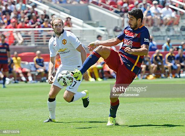 Luis Suarez of FC Barcelona controls the ball in front of the goal as defender Daley Blind of Manchester United looks on during the second half of...