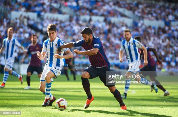 Luis Suarez of FC Barcelona duels for the ball with Aritz Elustondo of Real Sociedad during the La Liga match between Real Sociedad de Futbol and FC...