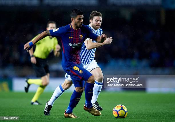 Luis Suarez of FC Barcelona duels for the ball with Asier Illarramendi of Real Sociedad during the La Liga match between Real Sociedad and FC...