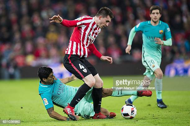Luis Suarez of FC Barcelona duels for the ball with Aymeric Laporte of Athletic Club during the Copa del Rey Round of 16 first leg match between...