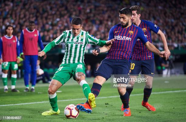 Luis Suarez of FC Barcelona duels for the ball with Cristian Tello of Real Betis Balompie during the La Liga match between Real Betis Balompie and FC...