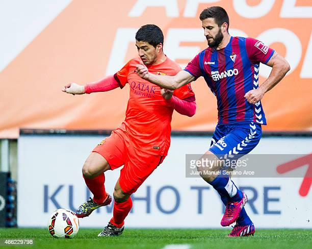 Luis Suarez of FC Barcelona duels for the ball with Raul Rodriguez Navas of SD Eibar during the La Liga match between SD Eibar and FC Barcelona at...