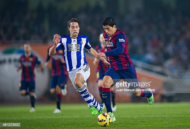 Luis Suarez of FC Barcelona duels for the ball with Sergio Canales of Real Sociedad during the La Liga match between Real Sociedad and Barcelona at...