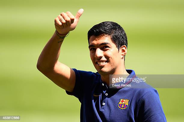 Luis Suarez of FC Barcelona gives his thumbs up during his presentation as new FC Barcelona player at Camp Nou on August 19 2014 in Barcelona Spain