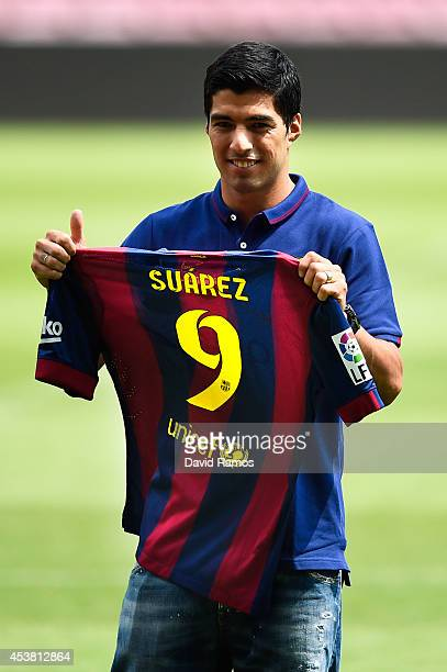 Luis Suarez of FC Barcelona holds a FC Barcelona shirt during his presentation as new FC Barcelona player at Camp Nou on August 19 2014 in Barcelona...