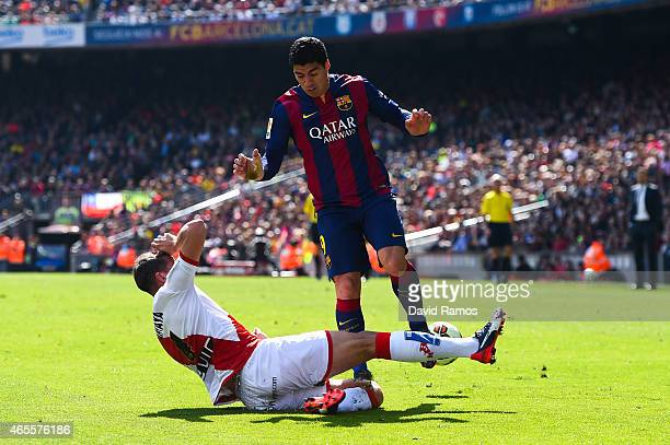 Luis Suarez of FC Barcelona is brought down by Antonio Amaya of Rayo Vallecano the La Liga match between FC Barcelona and Rayo Vallecano de Madrid at...