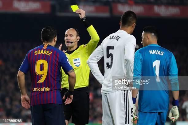 Luis Suarez of FC Barcelona is shown a yellow card by the referee Mateu Lahoz during the Copa del Semi Final first leg match between Barcelona and...
