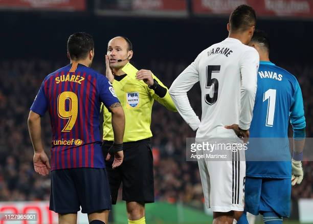 Luis Suarez of FC Barcelona is shown a yellow card by the referee Mateu Lahoz during the Copa del Rey Semi Final match between FC Barcelona and Real...