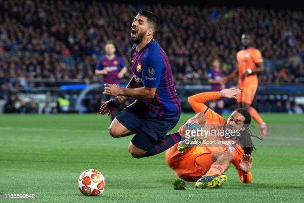 Luis Suarez of FC Barcelona is tackled by Jason Denayer of Olympique Lyonnais during the UEFA Champions League Round of 16 Second Leg match between...