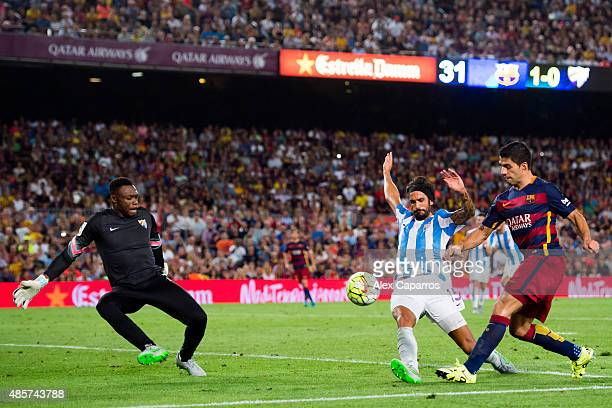 Luis Suarez of FC Barcelona kicks the ball next to Marcos Angeleri and Carlos Kameni of Malaga CF during the La Liga match between FC Barcelona and...