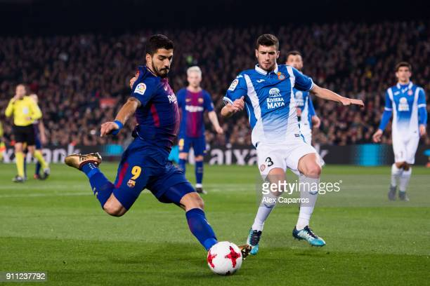 Luis Suarez of FC Barcelona plays the ball under pressure from Aaron Martin of RCD Espanyol during the Spanish Copa del Rey Quarter Final Second Leg...