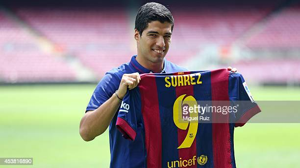 Luis Suarez of FC Barcelona poses with his shirt during his presentation as new FC Barcelona player at Camp Nou on August 19 2014 in Barcelona Spain