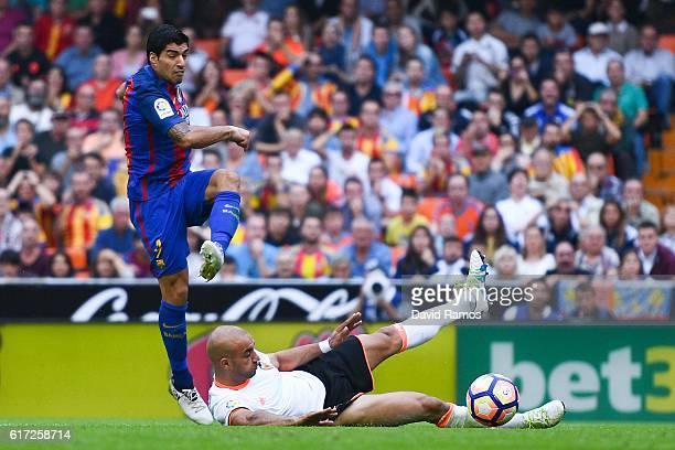 Luis Suarez of FC Barcelona scores his team's second goal past Aymen Abdennour of Valencia CF during the La Liga match between Valencia CF and FC...