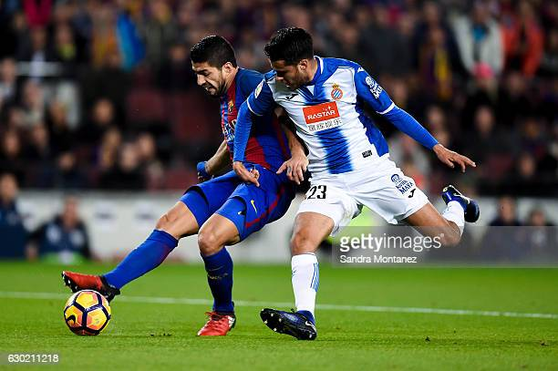 Luis Suarez of FC Barcelona scores the opening goal under a challenge by Diego Reyes of RCD Espanyol during the La Liga match between FC Barcelona...