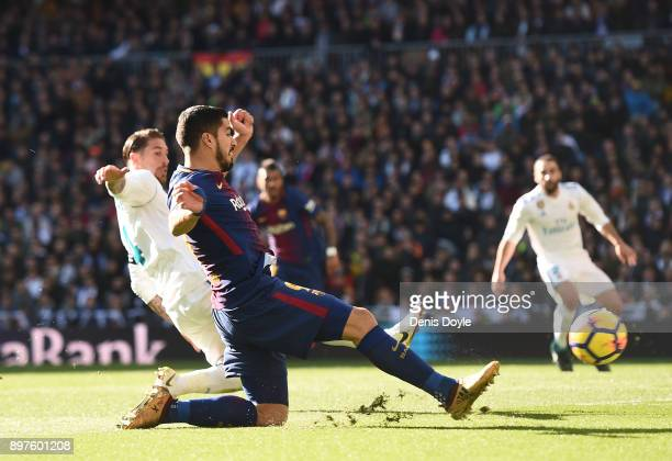 Luis Suarez of FC Barcelona shoots past Sergio Ramos of Real Madrid during the La Liga match between Real Madrid and Barcelona at Estadio Santiago...
