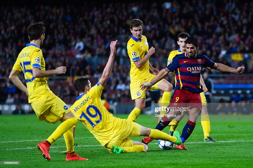 Luis Suarez of FC Barcelona shoots towards goal under a challenge by Nemanja Milunovic (2ndL) of FC BATE Borisov during the UEFA Champions League Group E match between FC Barcelona and FC BATE Borisov at the Camp Nou on November 4, 2015 in Barcelona, Spain.