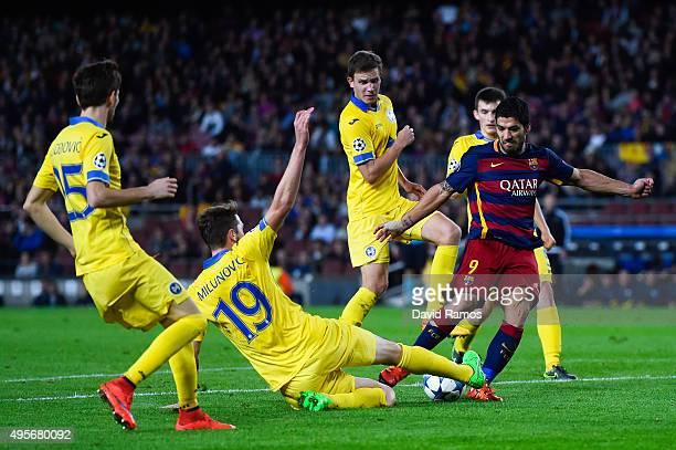 Luis Suarez of FC Barcelona shoots towards goal under a challenge by Nemanja Milunovic of FC BATE Borisov during the UEFA Champions League Group E...