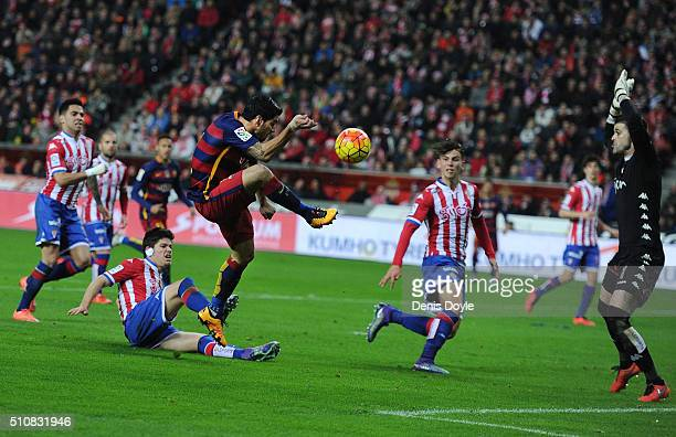 Luis Suarez of FC Barcelona tries to shoot over jumps Ivan Cuellar of Sporting Gijon during the La Liga match between Sporting Gijon and FC Barcelona...