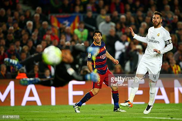 Luis Suarez of FC Barcelona watches his shot fly past Keylor Navas of Real Madrid CF and wide of the post as Sergio Ramos of Real Madrid CF looks on...
