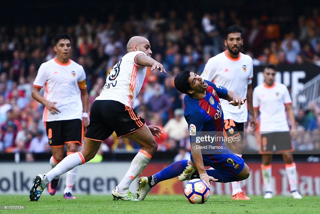 Luis Suarez of FC Barcelona wins a penalty as he is brought down by Aymen Abdennour of Valencia CF during the La Liga match between Valencia CF and FC Barcelona at Mestalla stadium on October 22, 2016 in Valencia, Spain.