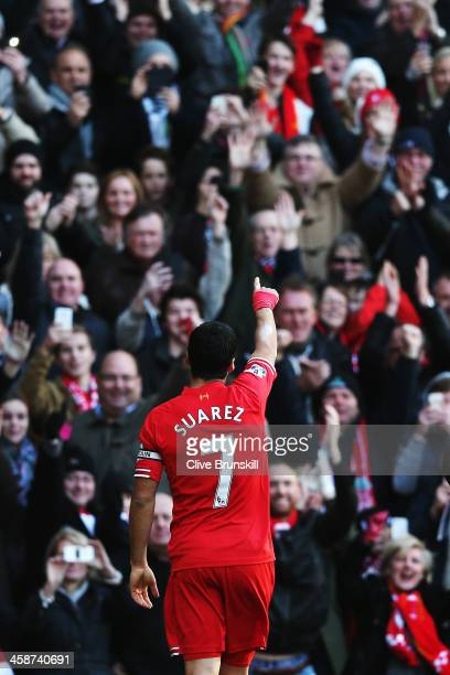 Luis Suarez of Liverpool acknowledges his sides fans after scoring during the Barclays Premier League match between Liverpool and Cardiff City at...