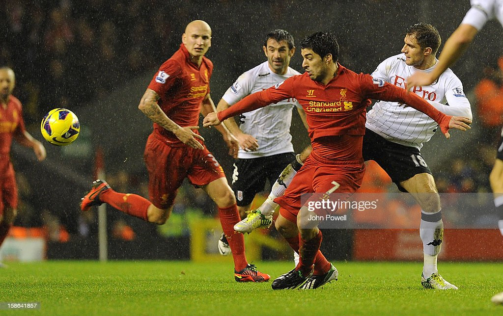 Luis Suarez of Liverpool and Aaron Hughes of Fulham compete during the Barclays Premier League match between liverpool and Fulham at Anfield on December 22, 2012 in Liverpool, England.