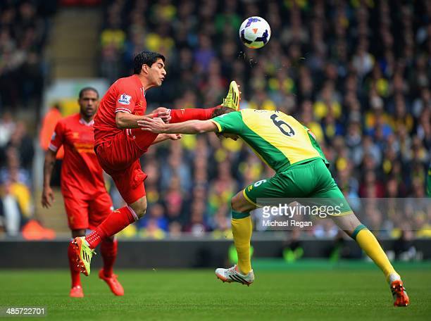 Luis Suarez of Liverpool and Michael Turner of Norwich City battle for the ball during the Barclays Premier League match between Norwich City and...