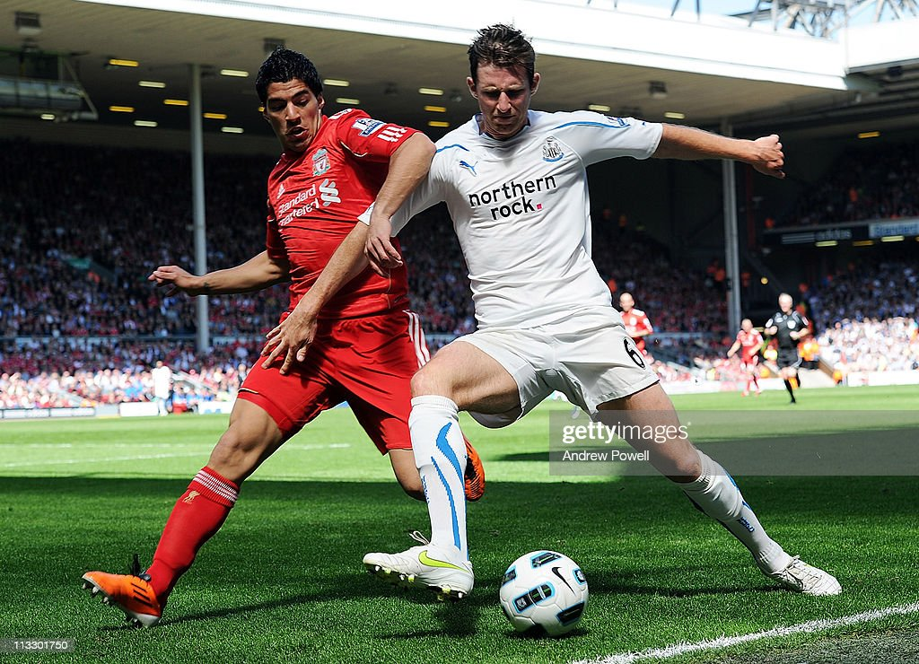 Luis Suarez of Liverpool and Mike Williams of Newcastle tussle during the Barclays Premier League match between Liverpool and Newcastle United at Anfield on May 1, 2011 in Liverpool, England.