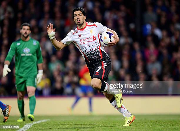 Luis Suarez of Liverpool celebrates after scoring his team's third goal as dejected goalkeeper Julian Speroni of Crystal Palace looks on during the...