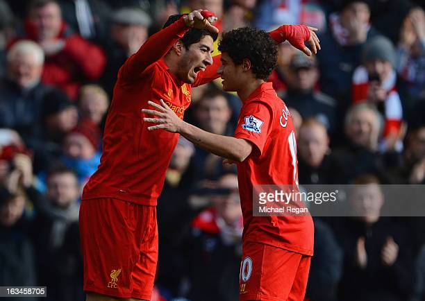 Luis Suarez of Liverpool celebrates his goal to make it 10 with Philippe Coutinho during the Barclays Premier League match between Liverpool and...