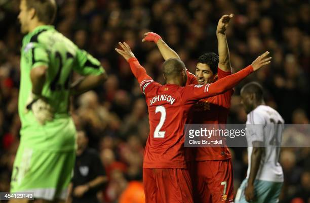 Luis Suarez of Liverpool celebrates scoring his team's third goal with team-mate Glen Johnson during the Barclays Premier League match between...
