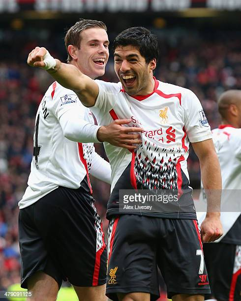 Luis Suarez of Liverpool celebrates scoring his team's third goal with teammate Jordan Henderson during the Barclays Premier League match between...