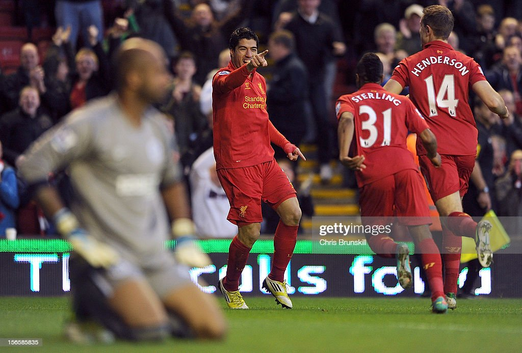 Luis Suarez of Liverpool celebrates scoring the opening goal with team-mates Raheem Sterling and Jordan Henderson as Ali Al Habsi of Wigan Athletic looks dejected during the Barclays Premier League match between Liverpool and Wigan Athletic at Anfield on November 17, 2012 in Liverpool, England.