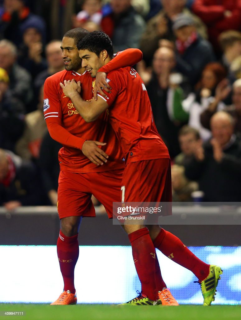 Luis Suarez of Liverpool celebrates scoring their second goal with Glen Johnson of Liverpool during the Barclays Premier League match between Liverpool and Hull City at Anfield on January 1, 2014 in Liverpool, England.