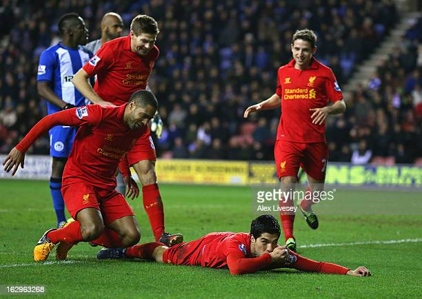 Luis Suarez of Liverpool celebrates with Glen Johnson and Steven Gerrard after scoring his third goal to complete a hat trick during the Barclays...