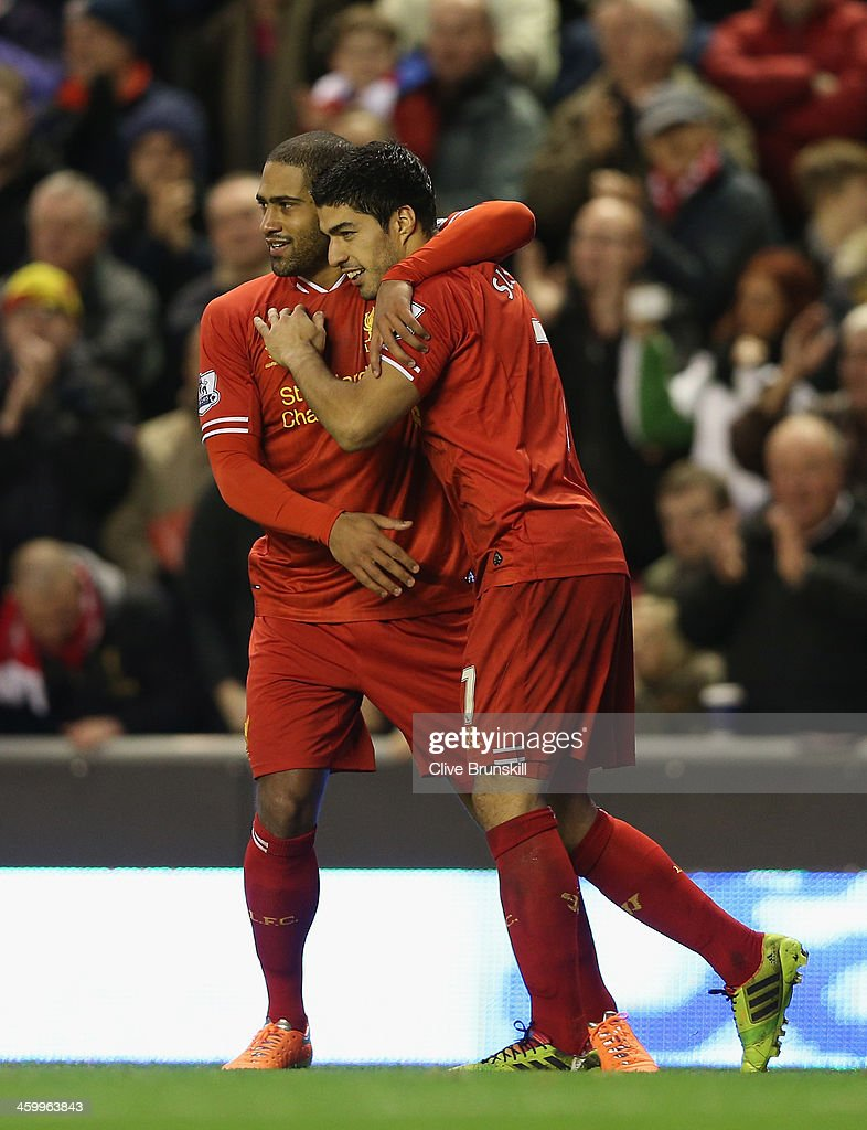 Luis Suarez of Liverpool celebrates with team mate Glen Johnson after scoring the second goal from a free kick during the Barclays Premier League match between Liverpool and Hull City at Anfield on January 1, 2014 in Liverpool, England.