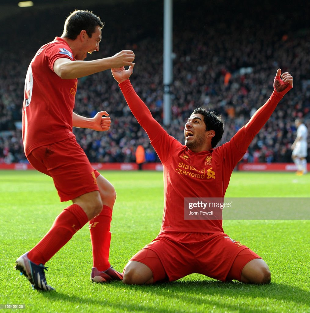 Luis Suarez (R) of Liverpool celebrates with team-mate Stewart Downing after scoring a goal during the Barclays Premier League match between Liverpool and Tottenham Hotspur at Anfield on March 10, 2013 in Liverpool, England.