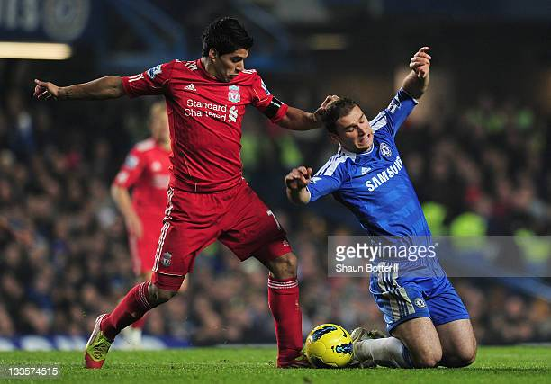 Luis Suarez of Liverpool challenges Branislav Ivanovic of Chelsea during the Barclays Premier League match between Chelsea and Liverpool at Stamford...