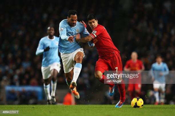 Luis Suarez of Liverpool challenges for the ball with Joleon Lescott of Manchester City during the Barclays Premier League match between Manchester...