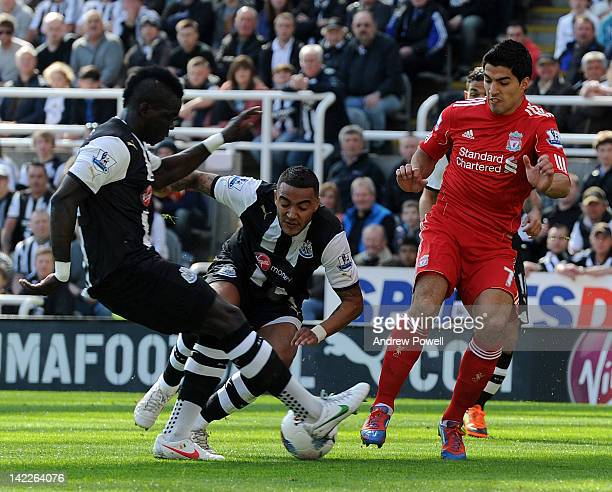 Luis Suarez of Liverpool competes with Cheick Tiote of Newcastle United during the Barclays Premier League match between Newcastle United and...