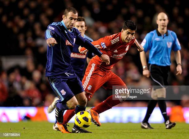 Luis Suarez of Liverpool competes with Danny Higginbotham of Stoke City during the Barclays Premier League match between Liverpool and Stoke City at...