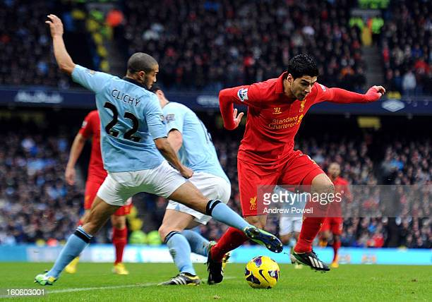 Luis Suarez of Liverpool competes with Gael Clichy of Manchester City during the Barclays Premier League match between Manchester City and Liverpool...
