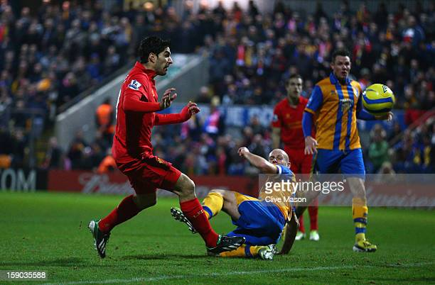 Luis Suarez of Liverpool goes around Alan Marriott of Mansfield Town to score during the FA Cup with Budweiser Third Round match between Mansfield...