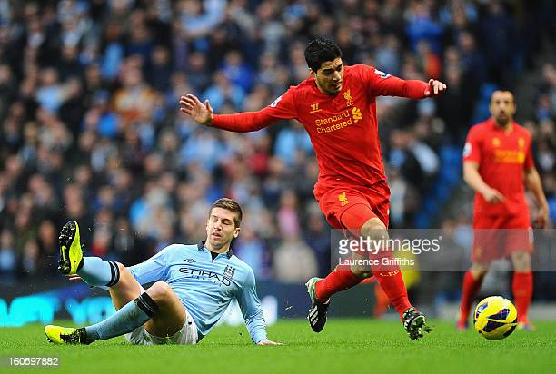 Luis Suarez of Liverpool goes past the challenge of Matija Nastasic of Manchester City during the Barclays Premier League match between Manchester...